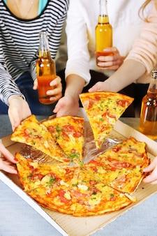 Mãos de amigos com garrafas de cerveja e pizza, close-up