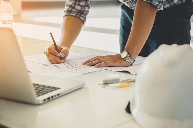 Mãos de arquiteto, trabalhando em planos de projeto com um lápis, uma régua, capacete, laptop e motor