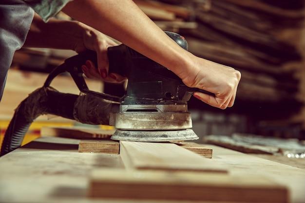 Mãos de artesã moendo madeiras com máquina especial. conceito de marcenaria e marcenaria. igualdade de gênero. profissão masculina