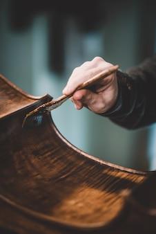 Mãos de artesão luthier envernizamento, construindo um contrabaixo