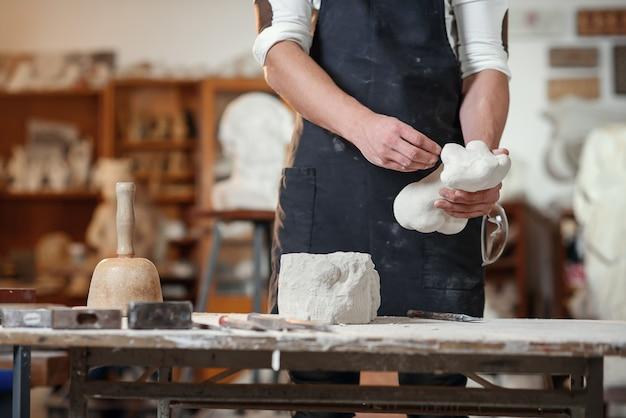 Mãos de artesão trabalhando com escultor de pedra no local de trabalho criativo no estúdio atmosférico.