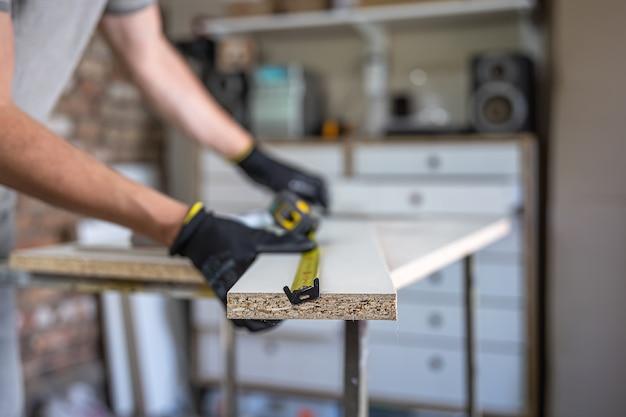 Mãos de artesão usando fita métrica e lápis para fazer marcas no pedaço de madeira colocado.