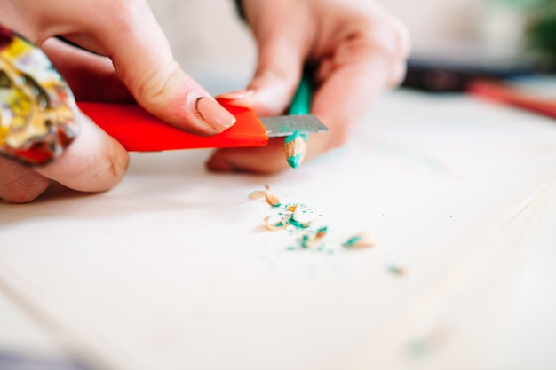 Mãos de artista afiando lápis com faca