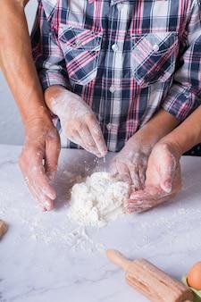 Mãos de avó e menino, neto cozinhando, amassando massa, assando torta, bolo, biscoitos. tempo para a família na cozinha aconchegante. atividade em casa.