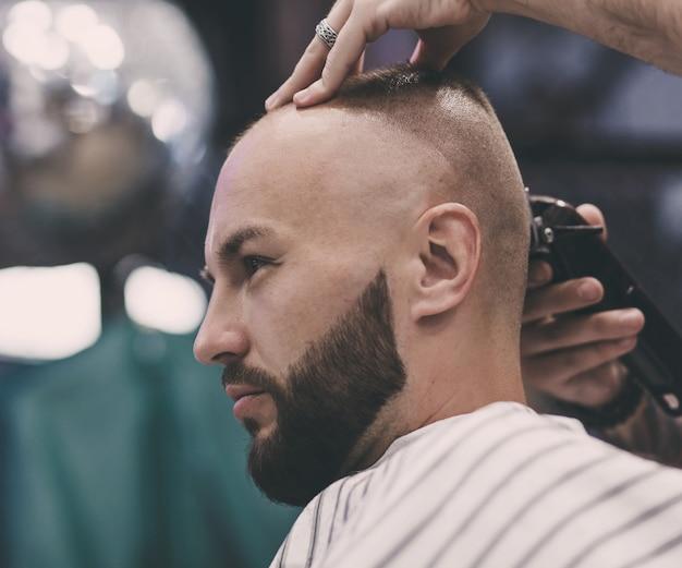 Mãos de barber e trabalho no cabelo do cliente.