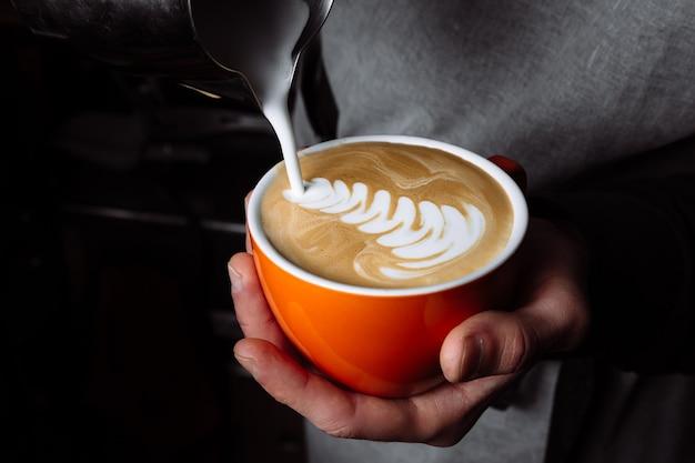 Mãos de barista derramando leite morno na xícara de café para fazer latte art.