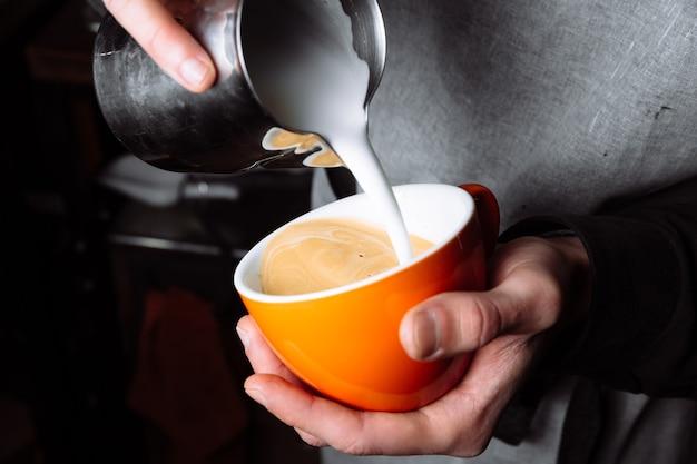 Mãos de barista derramando leite morno na xícara de café para fazer latte artm de perto