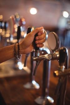 Mãos de barman usando torneira de cerveja em bar