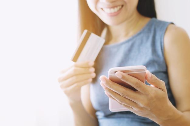 Mãos de belas garotas segurando um cartão de crédito e usando o celular, compras on-line ao ar livre, felizmente.