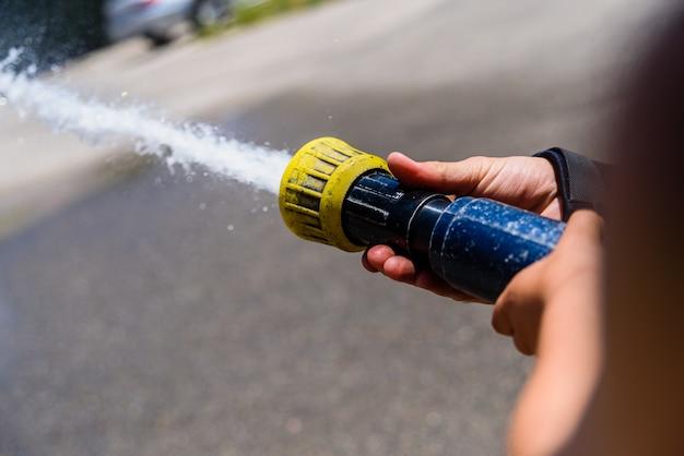 Mãos de bombeiro, sem rosto, segurando uma mangueira, jogando água a alta pressão.