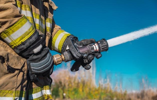 Mãos de bombeiro, sem rosto, segurando uma mangueira jogando água em alta pressão.