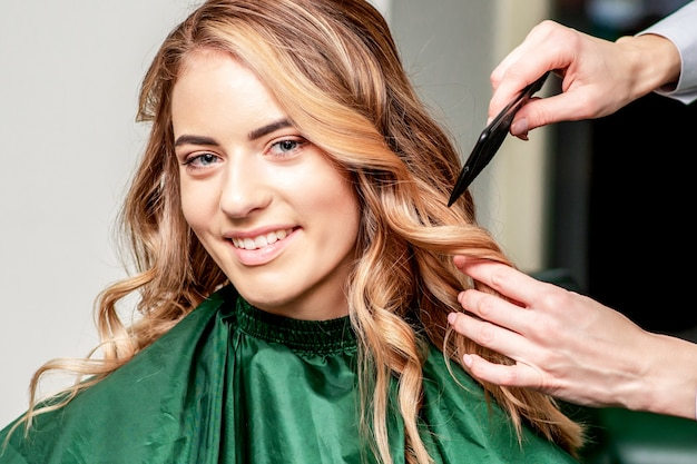 Mãos de cabeleireira penteando o cabelo de uma mulher sorridente em salão de cabeleireiro