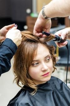 Mãos de cabeleireiro cabelo de mulher jovem