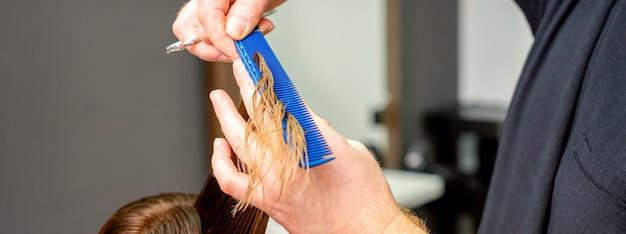 Mãos de cabeleireiro com pente e tesoura cortam o cabelo feminino molhado em um salão de cabeleireiro