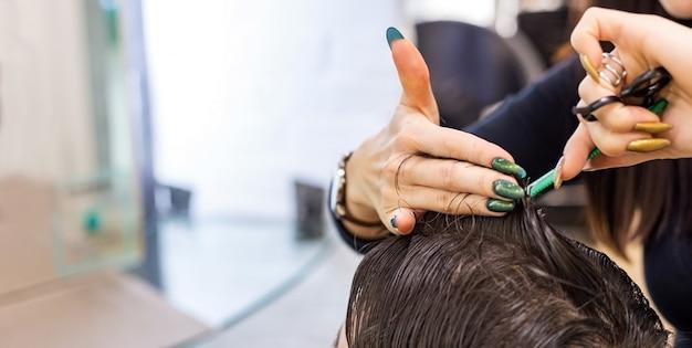 Mãos de cabeleireiro feminino fazendo corte de cabelo para cliente masculino usando uma tesoura de ferramentas de cabeleireiro profissional