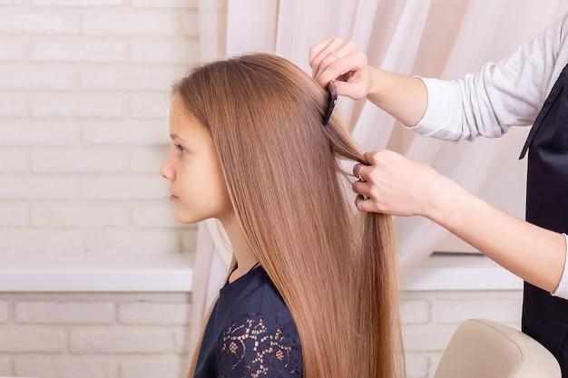 Mãos de cabeleireiro penteando o cabelo de uma menina