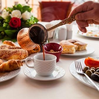 Mãos de café da manhã close-up com jezve derramando café em copo branco, bolos