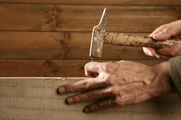 Mãos de carpinteiro com madeira de martelo e prego