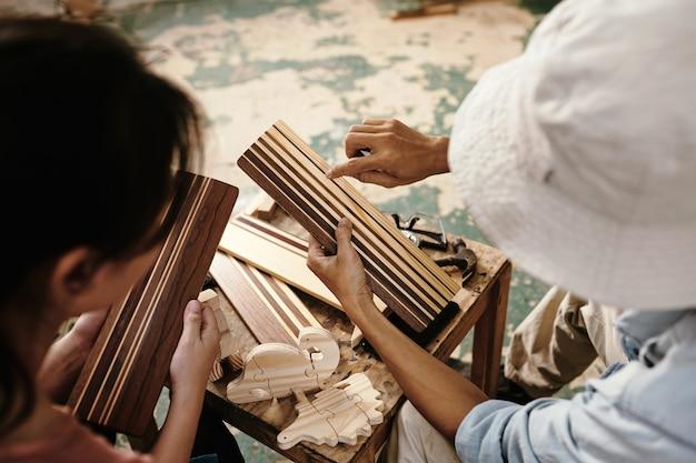 Mãos de carpinteiro mostrando uma prancha de madeira com listras de laca para um colega de trabalho quando eles estão discutindo o projeto