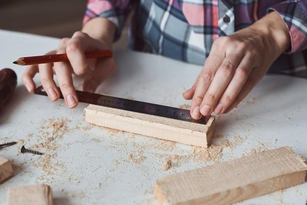 Mãos de carpinteiro, tomando a medida com lápis de prancha de madeira. conceito de madeira diy e fabricação de móveis