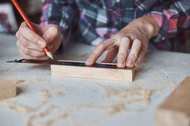 Mãos de carpinteiro, tomando a medida com lápis de prancha de madeira.