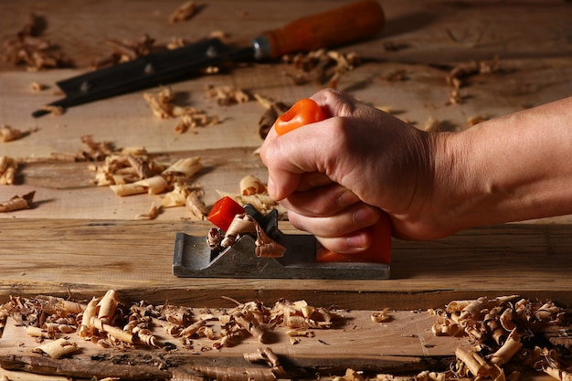 Mãos de carpinteiro trabalhando no processamento de madeira