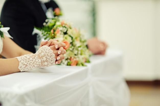 Mãos de casais de noivos na igreja católica