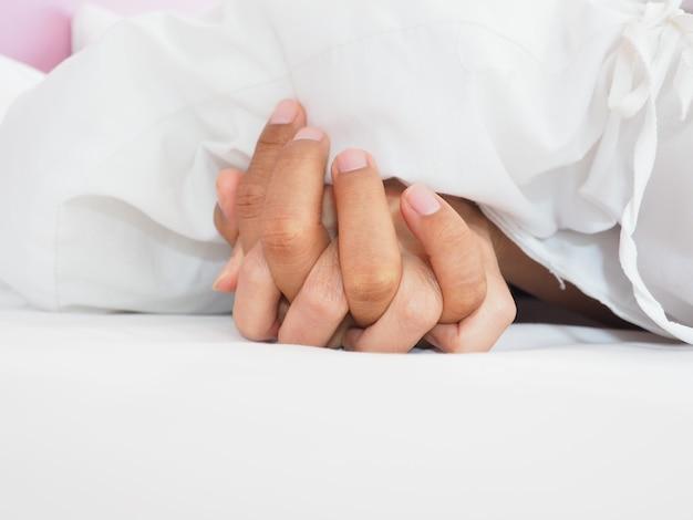 Mãos de casal amantes fazendo sexo em uma cama de manhã com luxúria e amor