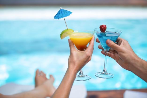 Mãos de casal brindando o copo de martini