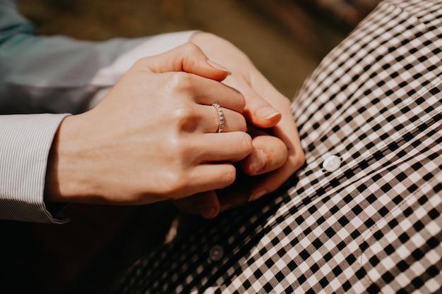 Mãos de casal. casal de amantes de mãos dadas. mão com anel