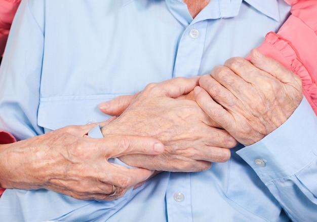 Mãos de casal de idosos, abraços
