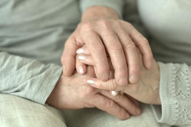 Mãos de casal de idosos afetuosos fecham-se