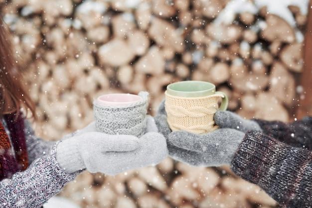 Mãos de casal em luvas de tomar canecas com chá quente em winter park