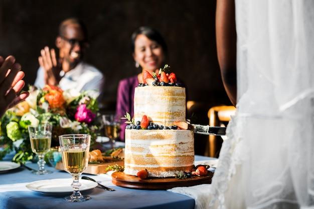 Mãos de casal recém-casado cortando bolo juntos
