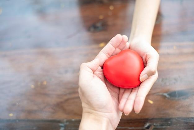 Mãos de casal segurando coração vermelho, amor e conceito de cuidados de saúde