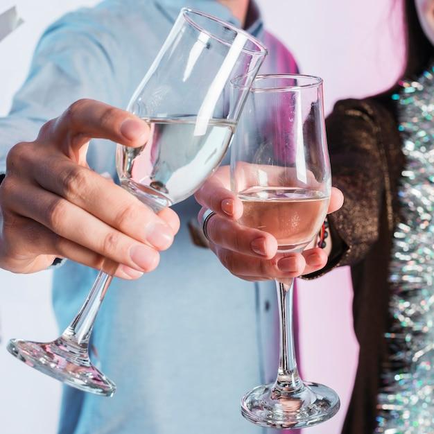 Mãos de casal tinindo copos de champanhe