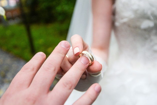 Mãos de casamento com anéis. birde usa o anel no dedo do noivo