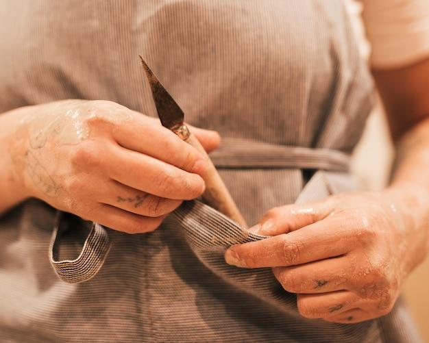 Mãos de ceramista segurando uma ferramenta de escultura do bolso