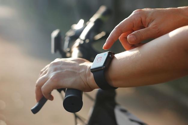 Mãos de ciclista de mulher com ícone de freqüência cardíaca no relógio inteligente, bicicleta na trilha de verão