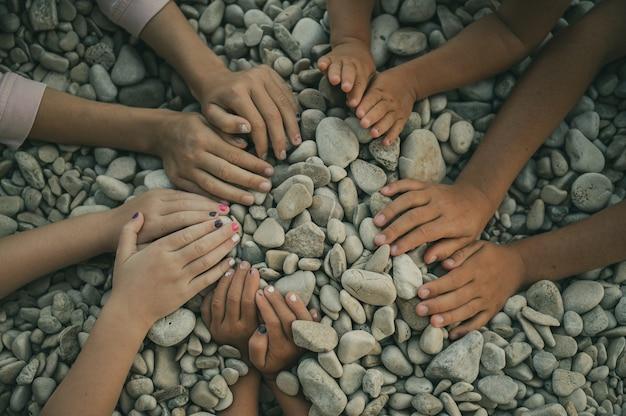 Mãos de cinco crianças fazendo um círculo sobre seixos.