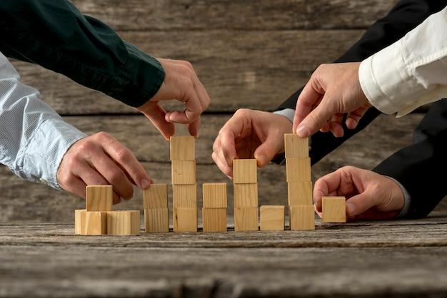 Mãos de cinco empresário segurando blocos de madeira, colocando-os em uma estrutura