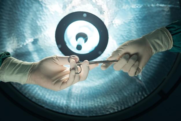 Mãos de cirurgiões segurando uma tesoura cirúrgica e passando o equipamento cirúrgico no fundo