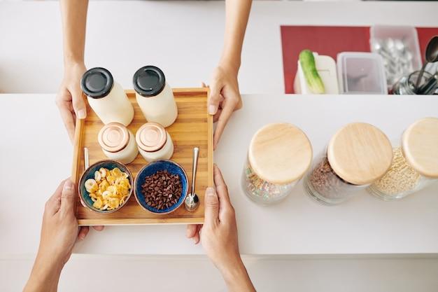 Mãos de clientes comprando café da manhã composto por iogurte fresco, flocos de milho e gotas de chocolate