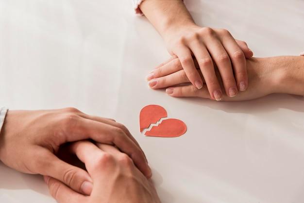 Mãos de close-up com coração partido