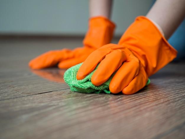 Mãos de close-up com luvas de borracha, limpando o chão