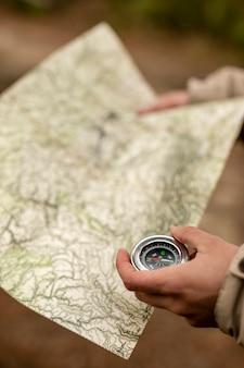 Mãos de close-up com mapa e bússola