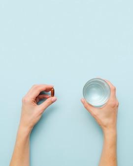 Mãos de close-up com pílula e água