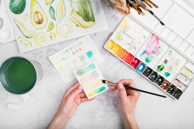Mãos de close-up com pincel e aquarelas