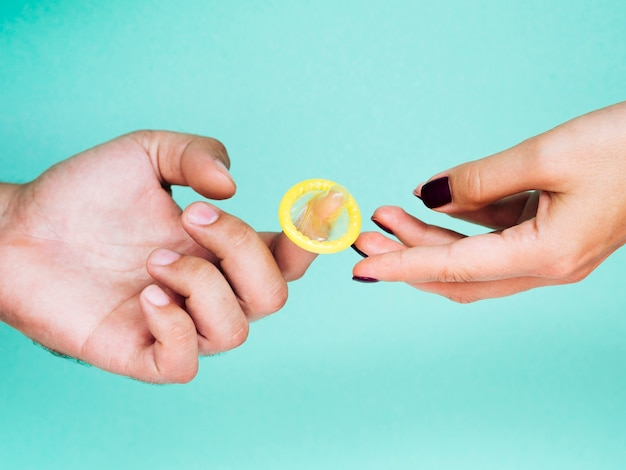 Mãos de close-up com preservativo amarelo desembrulhado