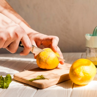 Mãos de close-up, corte de limão